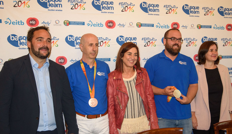 Cristina Uriarte (centro), Jon Redondo (izq.) y Olatz Legarza (drch.), junto con los deportistas paralímpicos medallistas