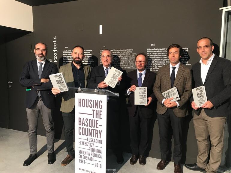 El consejero Arriola, flanqueado por Denis Itxaso y Pedro Jaúregui, muestra el catálogo de la exposición, acompañado por Pablo García-Astrain y los comisarios Asier Santas y Luis Suárez.