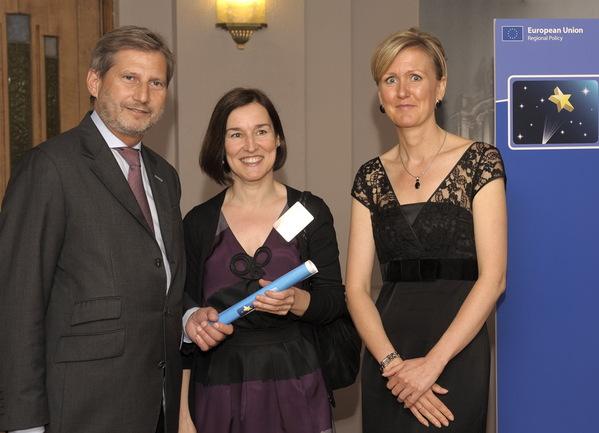 Maria Aguirre, en representación de Biobasque, recibe el premio de manos del Comisario Europeo para la Política Regional, Johannes Hahn, junto a la presidenta del jurado